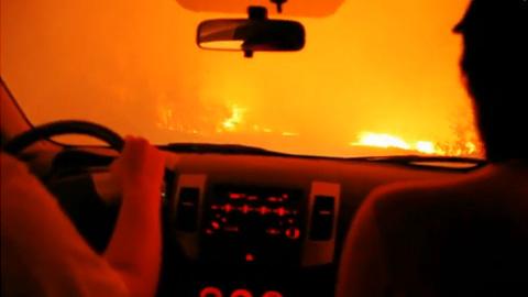 燃えさかる道路を車で脱出する男たち